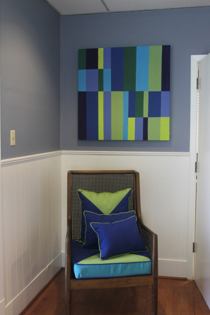 Periwinkle walls and white trim and wainscoting are a great backdrop for the vivid colors of blue and green in the art and accessories.