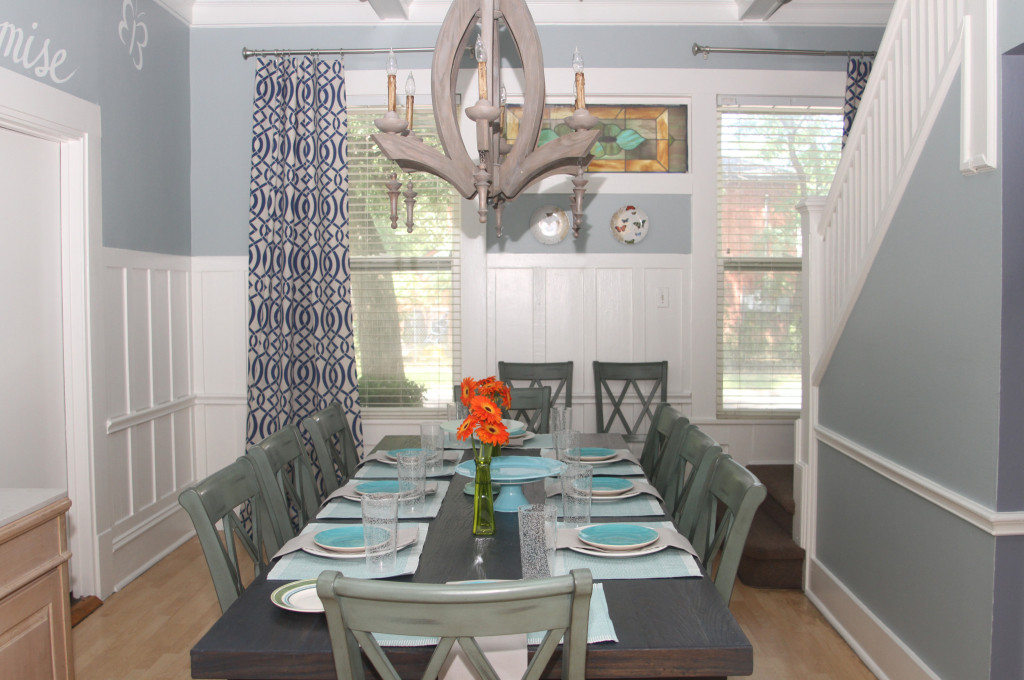 The dining room is now a tranquil blue and white with wood grain accents in the light fixture and furnishings.